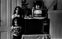 Two Girls with Two TVs, Undocumented Family, 1972, by Morrie Camhi, ©Estate of Morrie Camhi, Courtesy of Barry Singer Gallery